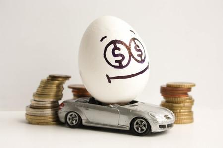 Bedrijfsconcept. Zakelijke auto. Een gelukkig ei met een geschilderd gezicht en een kleverige tong in het midden van een stapel munten. Ei op een grijze auto. Foto voor uw ontwerp