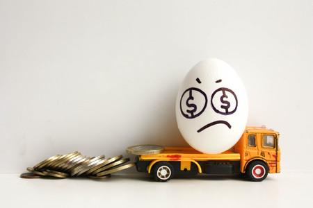 Bedrijfsconcept faillissement. Geldverlies. Een triest ei met een geverfd gezicht op een gele auto met verloren munten. Foto voor uw ontwerp Stockfoto
