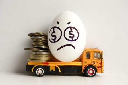 Bedrijfsconcept faillissement. Droevig ei met een geschilderd gezicht op een gele auto met muntstukken. Foto voor uw ontwerp Stockfoto