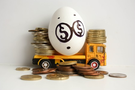 Bedrijfsconcept boekhouding. Een verrast ei met een geschilderd gezicht op een gele auto met munten. Foto voor uw ontwerp