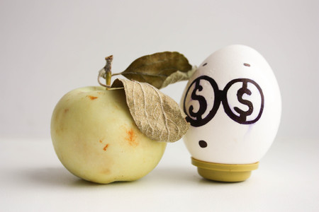 Business concept. An egg with dollar eyes and an apple is a bad business idea. Money apple. Photo for your design
