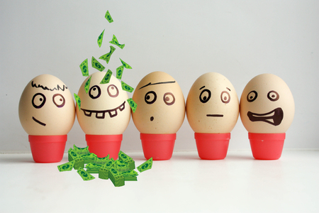 Business concept. Profitable business. Eggs with painted face. Concept of the first September lineup. Meeting calls roll call. Funny face photo for your design. With a lot of money, dollars pouring down on his head.