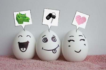 Concept of the idea of earning. Startup. Eggs are funny with faces. Concept of laughter. Photo for your design on a white background