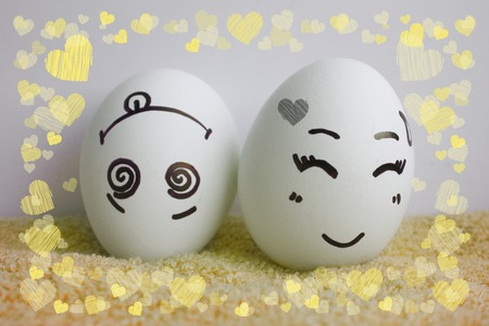 pareja comiendo: Eggs are cheerful with a face. Two pieces. Concept merry fellow. Photo for your design Frame of hearts. love Foto de archivo