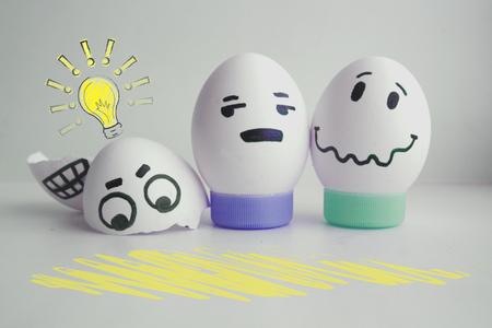 아이디어의 개념입니다. 빛. 스탠드 개념에 흰색 배경에 두 얼굴로 쾌활 한 계란 경고. 디자인을위한 사진
