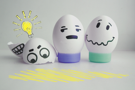 Concept of idea. Light. Cheerful eggs with two face on white background on stand concept warned. Photo for your design