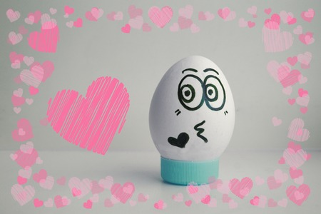 The egg is funny with the face on the stand. Concept: love feelings. Photo for your design on a white background Frame of hearts. love