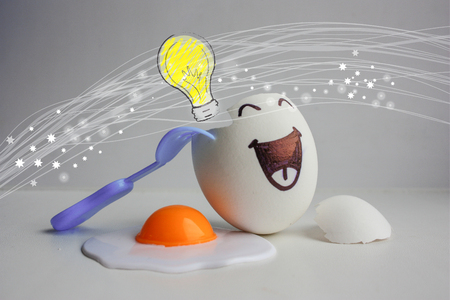 Eggs with face. Is there a brain, where is the brain, where is the mind . Photo for your design. Concept of the idea. Burning lamp.