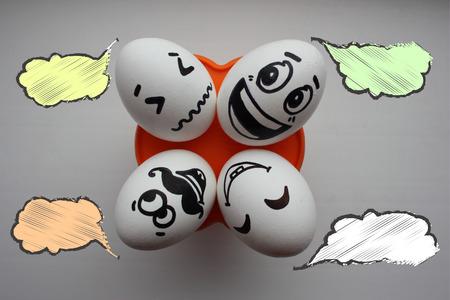 pareja comiendo: Huevos con una cara linda. Foto para su diseño. Cuatro huevos se encuentran y miran hacia arriba. Concepto: vacaciones familiares. La nube del pensamiento es blanca. Coloque debajo del texto.