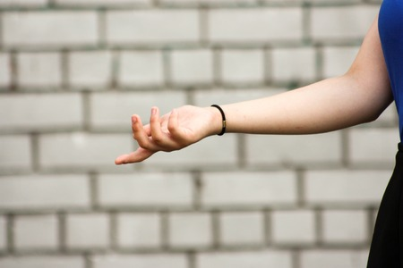 Learning concept. The girl is at the white brick wall. Photo for your design. Holds his hand open palm forward in the profile. Index finger forward. Stock Photo