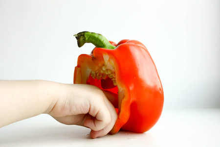 Pepper bulgarian red. A half is standing in front of a white background. The child to hold a rui in the inside. Photo for your design. Horizontal sheet orientation Stock Photo