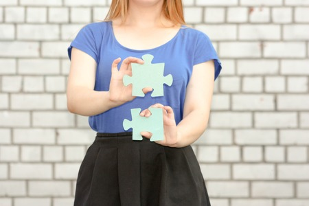 application university: Female student concept. Beautiful girl near a brick wall. Holds a puzzle upright in his hand. education system . Photo for your design