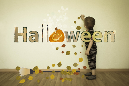 Halloween. the boy draws on the wall. pumpkin big and fucking broom with autumn leaves Фото со стока - 85632085