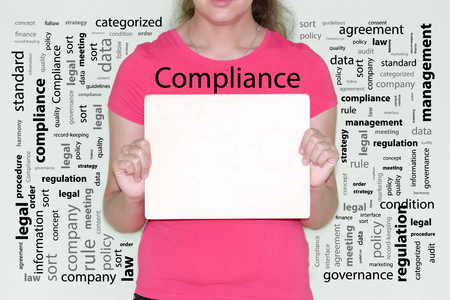 compliance concept. girl in red holds a wooden plaque in her hands Stock Photo - 85637882