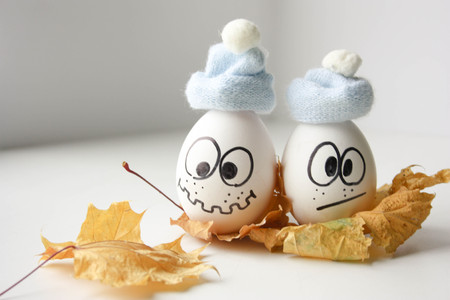 runny nose and chills concept fall. funny eggs float on the autumn leaf. horizontal sheet orientation
