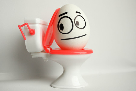 Constipation is a comical concept. an egg with a painted face sitting on the toilet. photo for your design.