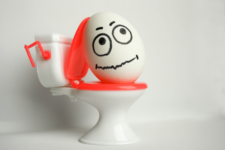 pain in abdomen concept comical. an egg with a painted face sitting on the toilet. photo for your design.