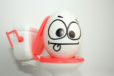 pain in abdomen concept comical. an egg with a painted face sitting on the toilet. shows the language. photo for your design.
