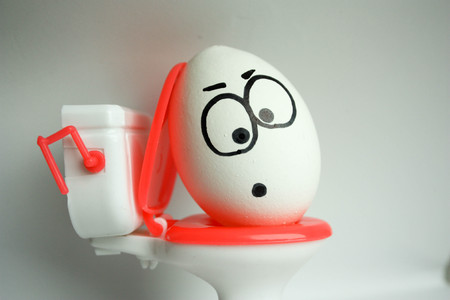 diarrhea is a comical concept. an egg with a painted face sitting on the toilet. photo for your design. Stock Photo