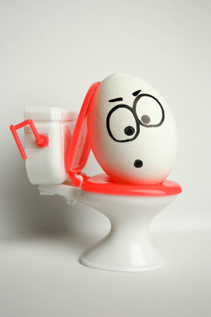 diarrhea is a comical concept. an egg with a painted face sitting on the toilet. photo for your design. vertical orientation