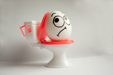 constipation abdominal pain concept. funny egg on the toilet. photo for your design
