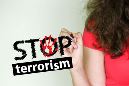 stop terrorism concept. girl in red writes a marker on a light background