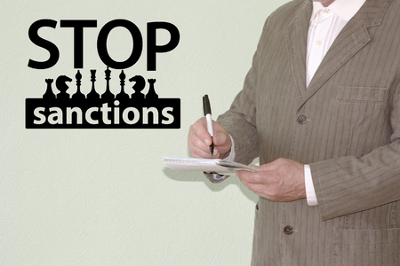 STOP SANCTIONS CONCEPT. POLITICAL GAME. a man in a jacket with a notebook and a pen in his hand