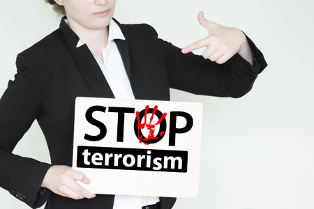 stop terrorism concept. inscription on a wooden sign girl in a jacket points to