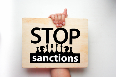 stop sanctions concept. the inscription on the wooden plaque is horizontal