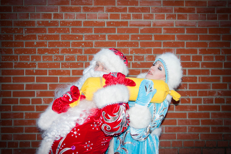 santa claus and miss santa claus with a big yellow candy. sweets for the holiday