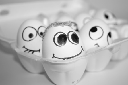 hairstyle elevated concept. the eggs are funny and cute. photo with painted face on the shell. satire and comedy. eggs with hair on the head. eggs in a box