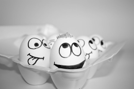 the idea came up with a concept. the eggs are funny and cute. photo with painted face on the shell. satire and comedy. egg with hair on head Banco de Imagens