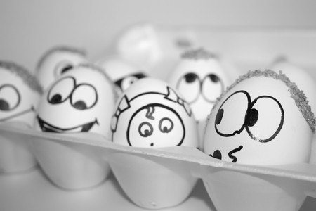 kind house concept. the eggs are funny and cute. photo with painted face on the shell. satire and comedy. an egg with a hair on his head with a huge smile. a dozen eggs. many eggs