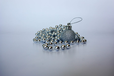 Christmas tree. decoration for spruce. silver beads. photo for your design. pile of round beads with a Christmas tree in sequins Stock Photo