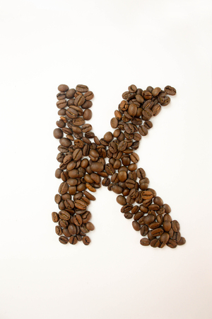 K the letter. alphabet of coffee. coffee beans. concept of healthy eating. photo for your design. vertical orientation of the sheet Stock Photo