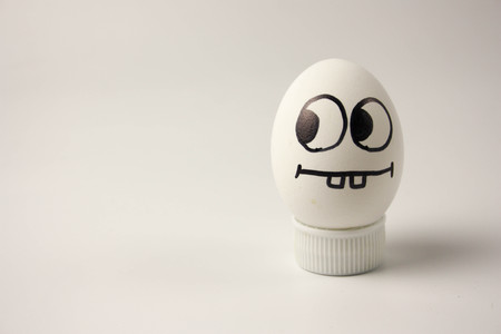 simplicity concept. cute and funny egg with painted face and hair. photo for your design