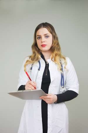 doctor therapist with a history of the patient's illness .. doctor blond girl smiling. on a white background. red bright lips. vertical sheet orientation