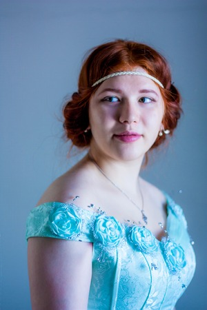 smiling tender girl. Portrait of a beautiful red-haired girl. baroque. in a blue ball gown. vertical sheet orientation