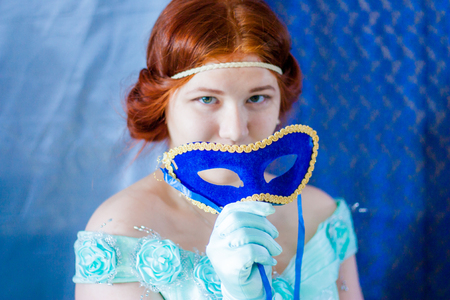 masquerade. portrait of a tender red-haired girl. in a blue historical dress. holds a mask in his hand
