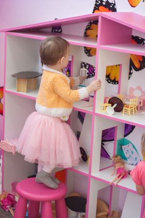 Dollhouse. little girl in all pink plays with dolls on a pink chair Stock Photo