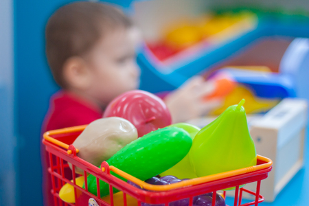 Shopping cart. fruits and vegetables. a useful purchase. child at the cash register