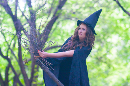 Halloween. The witch is funny. Old broom, bald whisk. Unwitting witch in the hood of the witch