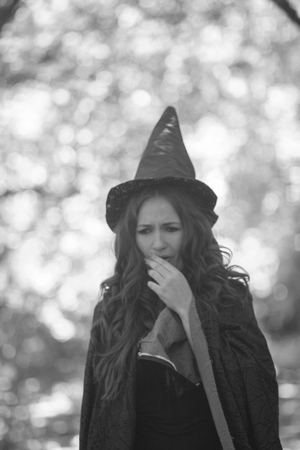 a witch cute witch. an attractive girl in a cap whispers a plot. spell Reklamní fotografie