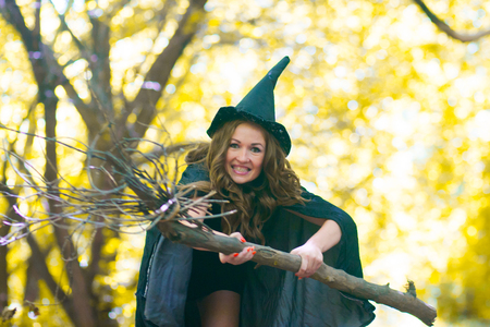 a witch on a broomstick among the forest. Portrait of a cute girl. mischievous sorceress. sexy girl with a broom and a witch hood in a raincoat 免版税图像