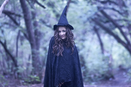 a witch in a hood and a cloak in the forest. Portrait of a cute girl. learning magic. school of magic. student magician Stock Photo