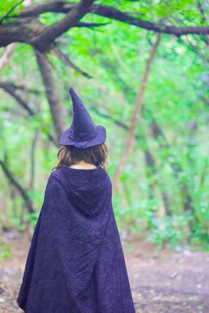 a witch in a hood and a cloak in the forest. concept of halloween