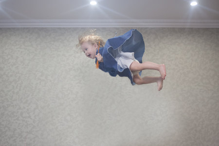 JUMPING CEILING. a little girl is lightening under the ceiling in the rays of light from the lamps in a blue dress Reklamní fotografie
