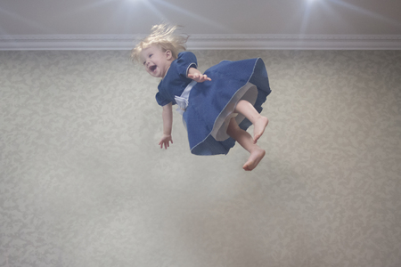 dive into the air. little girl is lightening under the ceiling Banco de Imagens