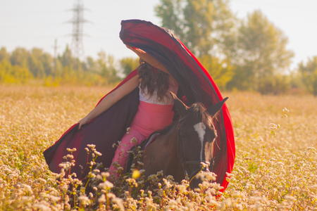 beautiful girl, brunette in a red raincoat. on horseback riding. among the buckwheat field. summer and rest. walks on horseback. whirlwind Imagens