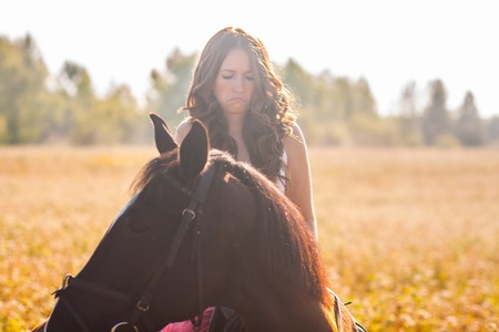 Doubting girl on a horse in a dress in the sun on the field
